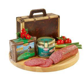 Bruchsicher konfektioniert im Kartonkoffer mit Tragegriff und im Umkarton versandfertig verpackt. Ein Stück Salami 1a, weiß, 300 g, ein Glas gekochte Mettwurst im Glas, 250 g, Spitzenqualität, ein Paket Vollkornbrot, 500 g, extra saftig und aus vollem Korn. Zutaten: Salami: Schweinefleisch, Speck, Salz, Gewürze, Dextrose, Zucker., gekochte Mettwurst: Schweinefleisch, Salz, Gewürze, Kräuter., Vollkornbrot: Roggenvollkornschrot, Salz, SAUERTEIG, Wasser.. Allergiehinweis: Salami: Kann Spuren allergener Stoffe nach Anlage LMIV enthalten.  gekochte Mettwurst: Kann Spuren von Sellerie und Senf enthalten.<br>