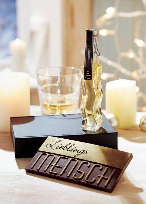 Für die besonders lieben Menschen ist dieses Geschenk-Set ganz besonders gut geeignet. Eine 100g Tafel Schokolade mit Gold-Design Lieblingsmensch, eine 40 ml Whisky Sir Williams in der Bügelflasche, Verpackt in einem schicken schwarzen Präsentkarton, Gewicht: ca. 0,3 kg. Zutaten: Whisky: Alkohol, Wasser, Caramel (Mais- und GERSTENmalz), Schokolade: Kakaomasse, Zucker, Kakaobutter, Emulgator: SOJAlecithin, Vanilleextrakt, Farbstoff E 171, E 172, Überzugsmittel:Schellack. Nährwertangaben: Schokotafel: Brennwert 2369 kJ / 568 kcal; Fett 43 g, davon gesättigte Fettsäuren 25g; Kohlenhydrate 40g, davon Zucker 37g; Eiweiß 5,7g; Salz 0,01g. Allergiehinweis: Kann Spuren von Milchbestandteilen, Haselnüssen und anderen Schalenfrüchten enthalten.<br>