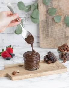 Hier ist ein zuckerfreies Nutella von vorne fotografiert zu sehen. Das Nutella wurde in einem Glas schön angerichtet und mit einem Löffel wird etwas von dem Nutella herausgelöffelt. Im Hintergrund steht ein altes Holzbrett und man sieht Eukalyptusblätter herunter hängen.