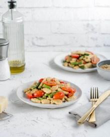 Hier sind Gnocchi mit grünem Spargel und Kirschtomaten zu sehen. Die Gnocchi wurden auf zwei weißen Tellern angerichtet und im Hintergrund steht eine Flasche mit Olivenöl und einem Salzstreuer.