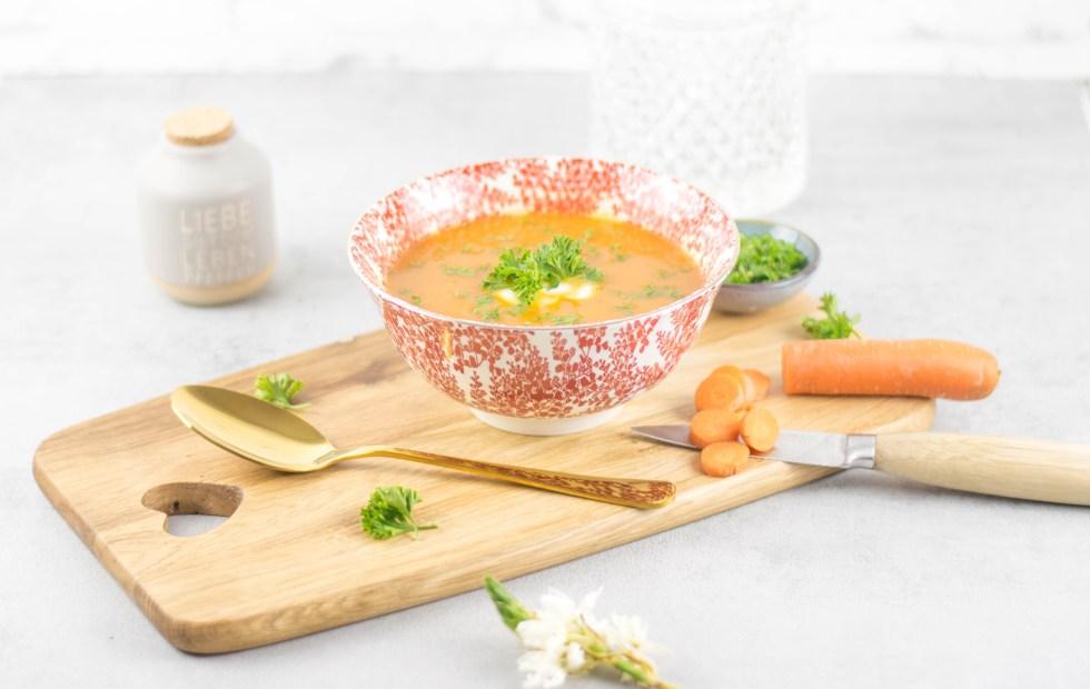Türkische rote Linsen Suppe in einer orientalischen Schüssel, die auf einem Holzbrett steht. Davor liegt ein goldener Löffel und im Hintergrund steht ein orientalisches Glasgefäß. Am Holzbrett liegt eine angeschnittene Karotte und dahinter klein gehackte Petersilie.