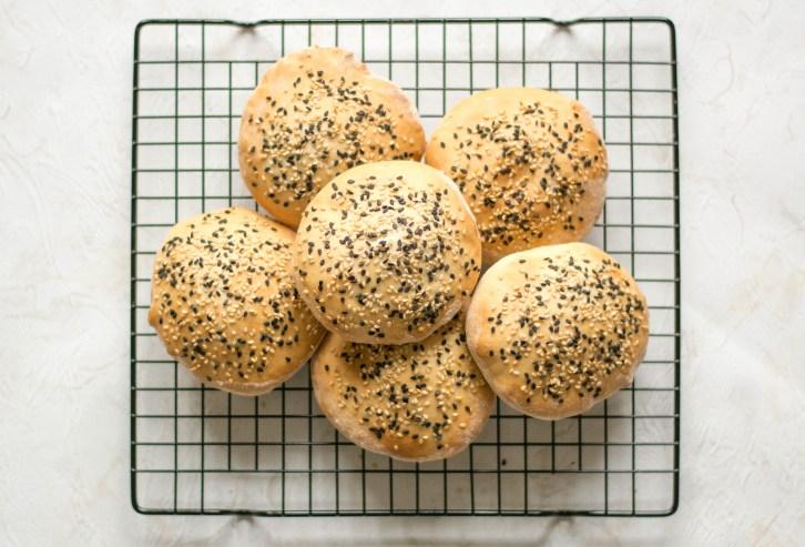 Auf dem Bild sind Burger Brötchen mit weißem und schwarzem Sesam zu sehen. Die Brötchen wurden von oben fotografiert und liegen auf einem schwarzen Backgitter.