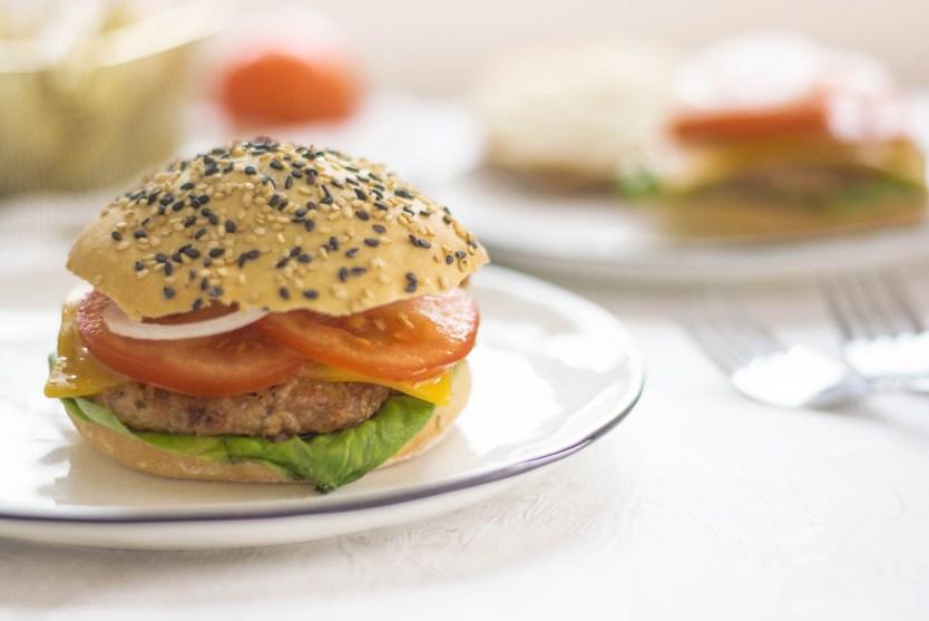 Jackfrucht - Burger mit Jackfrucht - Laibchen von vorne fotografiert. In dem Burger sieht man frische Tomaten, einen Salat und Zwiebelringe.