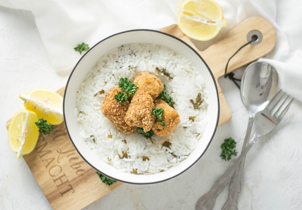 Knusper Jackfrucht im Sesam - Mantel mit Zitronen - Petersilienreis in einer weißen Schüssel von oben fotografiert. Die Schüssel steht auf einem Holzbrett. Daneben liegen Zitronen und frische Petersilie.