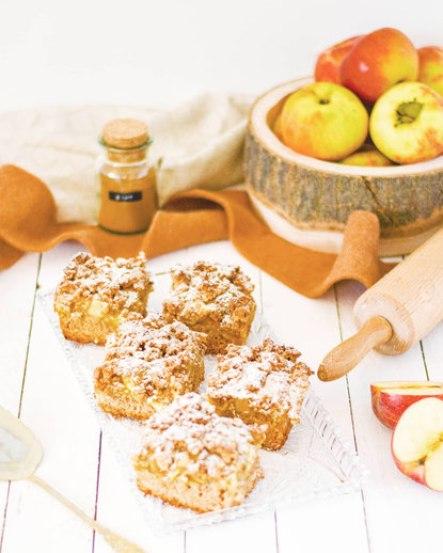 Zuckerfreier Streuselkuchen von vorne fotografiert. Die Äpfel liegen im Hintergrund in einer alten Holzschale. Daneben steht ein Gläschen Zimt.