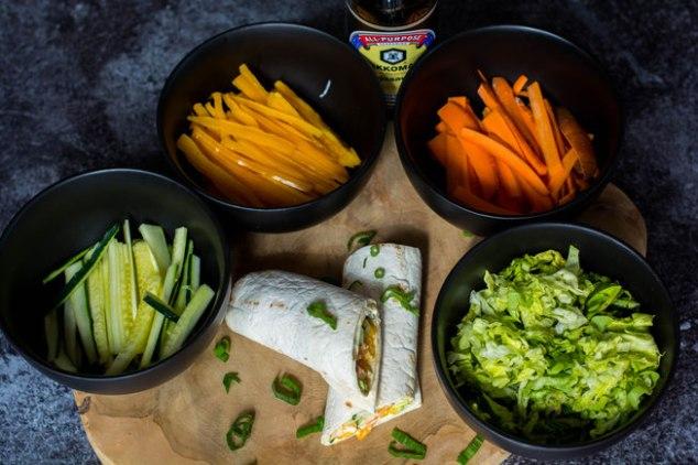 Auf dem Bild sind asiatische Wraps zu sehen. Um die Wraps herum stehen mehrere schwarze Schüsseln mit geschnittenem Gemüse.
