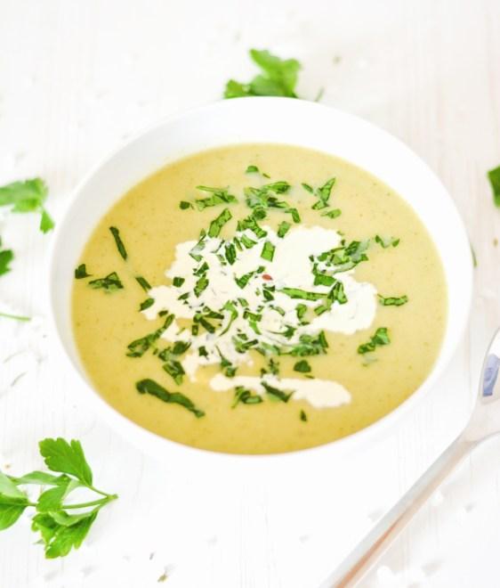 Auf diesem Bild ist eine Brokkolicremesuppe von oben fotogrfiert zu sehen. Die Brokkolicremesuppe wurde mit Sahne und frischen Kräutern angerichtet.