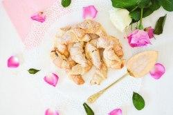 Auf diesem Bild sind zuckerfreie Quark Kipferl mit Marmelade zu sehen. Die Kipferl liegen auf einem weißen Tisch, daneben liegt ein Tortenheber und rosarote Rosenblüten.