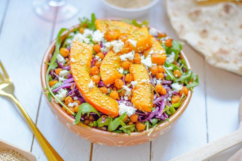 Orientalischer Herbstsalat mit Kürbis von vorne fotografiert. Daneben liegt eine goldene Gabel und ein Tortilla.