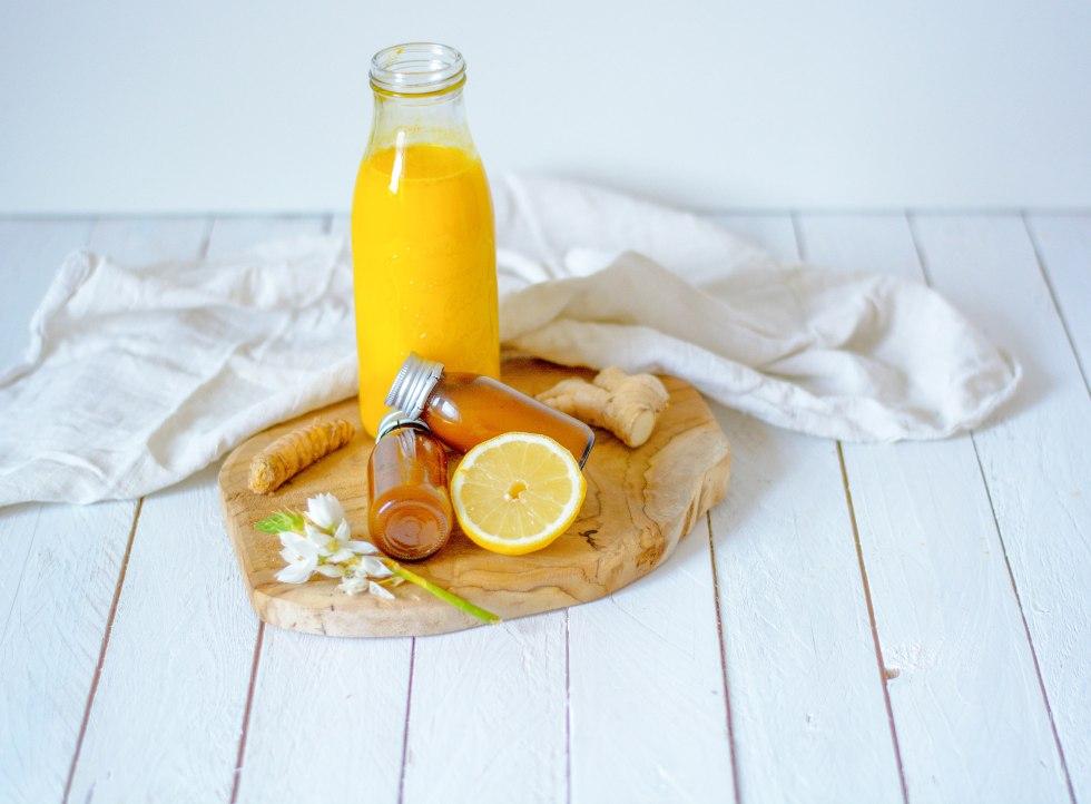 Auf diesem Bild ist ein Kurkuma - Ingwer Shot zu sehen. Der Shot steht auf einem Holzbrett. Daneben liegen Ingwer, Kurkuma und Zitrone.