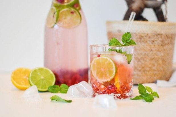 Auf dem Bild ist ein Erfrischungsgetränk mit Himbeeren und Limetten zu sehen. Im Hintergrund steht ein großer Krug mit dem Getränk. Im Vordergrund steht ein schönes Glas mit einem Glasstrohhalm und dem Erfrischungsgetränk.