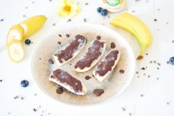 Auf diesem Bild ist eine gefrorene Snickersbanane zu sehen. Die Banane liegt auf einem Teller, daneben sieht man Kakaonibs liegen.