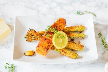 Hier ist ein parnierter Parmesan - Spargel aus dem Backofen mit Lachs zu sehen. Der Spargel liegt auf einem Teller, darauf ist der Lachs zu sehen und eine Scheibe Zitrone. Im Hintergrund lieft ein Parmesan und frische Kräuter.