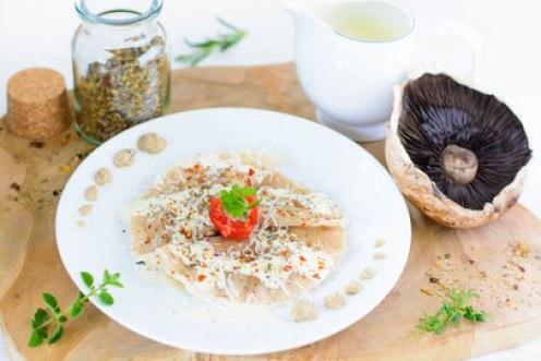 Auf dem Bild sind Ravioli mit Pilzfüllung zu sehen. Die Ravioli wurden aus einem 40 ° Winkel fotografiert. Daneben liegen ein Kräuterseitling, Kräuter und die Kräuter - Sahne Sauce.