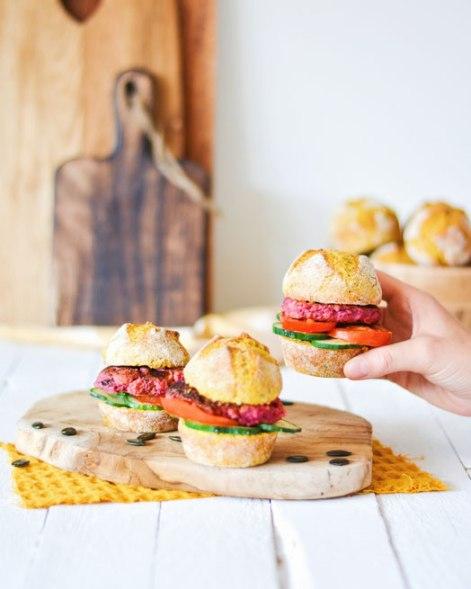 Auf dem Bild sind Burger mit rote Rüben Laibchen und Bürgerweckerl zu sehen. Einer der Burger wird von einer Hand hochgehoben. Im Hintergrund stehen alte Holzbretter.