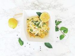 Zitronen - Zucchini Spaghetti von oben fotografiert. Daneben liegen frische Minzblätter.