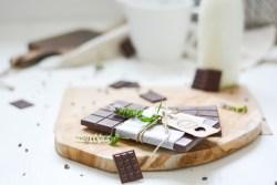 Auf diesem Bild ist eine zuckerfreie Schokolade zu sehen. Die Schokolade liegt auf einem Holzbrett und im Hintergrund steht eine Flasche Milch. Die zuckerfreie Schokolade ist schön eingepackt und kann so auch gleich verschenkt werden.