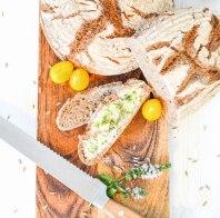 Vollkornbrot von oben fotografiert. Eine Scheibe Brot ist bereits mit Butter bestrichen.