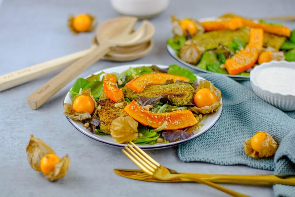 Auf dem Bild ist ein Zucchini in Kürbiskernpanade und in Sesam gebratenem Kürbis mit gemischtem Salat zu sehen.