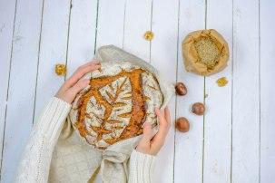 Hier ist ein Brot zu sehen, welches von oben fotografiert wurde. Das Brot wird links und rechts von zwei Händen gehalten. Das Bild wurde von oben aufgenommen.