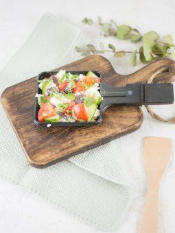 Auf diesem Bild ist ein Raclette Pfännchen mit warmen griechischen Salat zu sehen. Das Pfännchen steht auf einem alten Holzbrett und ist von grünen Blättern umgeben.