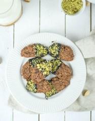 Zuckerfreie Nutella - Plätzchen von oben fotografiert. Sie liegen auf einem weißen Keramik - Teller und sind mit einer Hälfte mit Schokolade überzogen und mit Pistazienkernen verziert.
