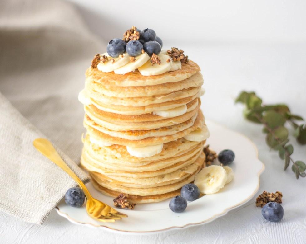 Auf diesem Bild sind zuckerfreie Quark Pancakes von vorne zu sehen. Sie liegen gestapelt auf einem Teller und sind mit Bananen und Heidelbeeren verziert.