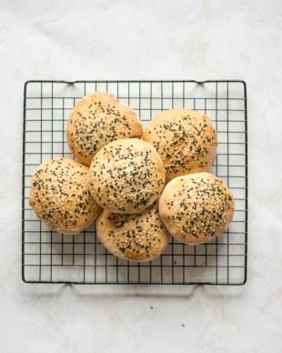 Burger Brötchen von oben fotografiert. Sie liegen auf einem schwarzen Backgitter und sind mit weißem und schwarzem Sesam bestreut.