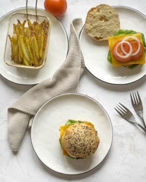 Jackfrucht Burger von oben fotografiert. Es liegen drei Teller auf dem Tisch. Auf einem Teller sind Pommes zu sehen. Auf dem 2. Teller liegt ein Burger Brötchen, welches gerade zubereitet wird und am letzten liegt ein fertiger Burger.