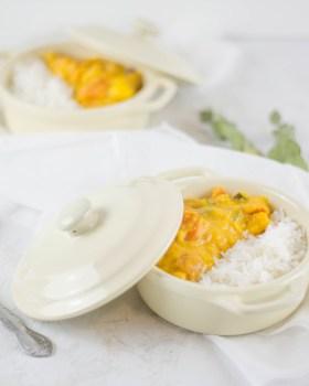 Auf dem Bild ist ein Kürbis Curry mit Reis in einem kleinen cremefarbenen Topf zu sehen.