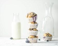 Auf diesem Bild sind zuckerfreie Heidelbeeren Muffins zu sehen. Sie wurden übereinander gestapelt und im Hintergrund stehen Gläser und eine Flasche Milch. Daneben liegen mehrere frische Heidelbeeren.