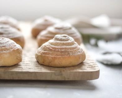 Vegane Nussschnecken von vorne fotografiert. Die Nusschnecken liegen der Reihe nach auf einem Holzbrett vor einem hellen und weißen Hintergrund.