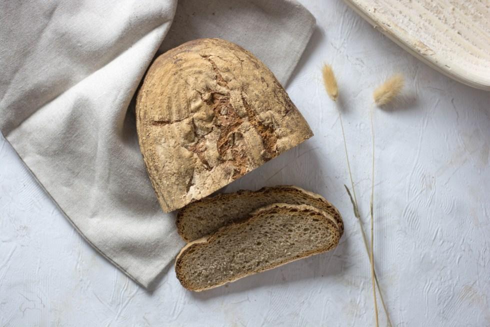 Auf diesem Bild ist ein einfaches Sauerteigbrot zu sehen. Das Brot liegt auf einem weißen Untergrund. Daneben liegt ein Leinentuch und getrocknete Gräser sowie ein Gärkörbchen.