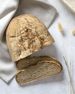 Hier ist ein einfaches Sauerteigbrot auf einem weißen Untergrund und beigen Bäckerleinen zu sehen.