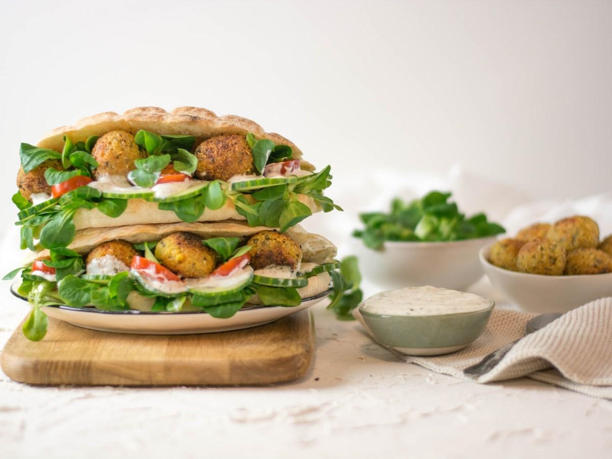 Hier ist eine Falafel - Fertigmischung zu sehen und daneben liegen Fladenbrote mit Salat, Joghurtsoße und Falafel gefüllt.