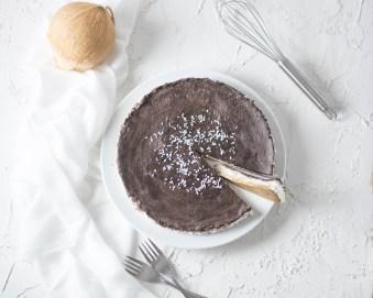 """Auf diesem Bild ist eine zuckerfreie """"no bake"""" Bounty Torte zu sehen. Die Bounty Torte wurde von oben fotografiert und daneben liegen ein Schneebesen und eine Kokosnuss."""