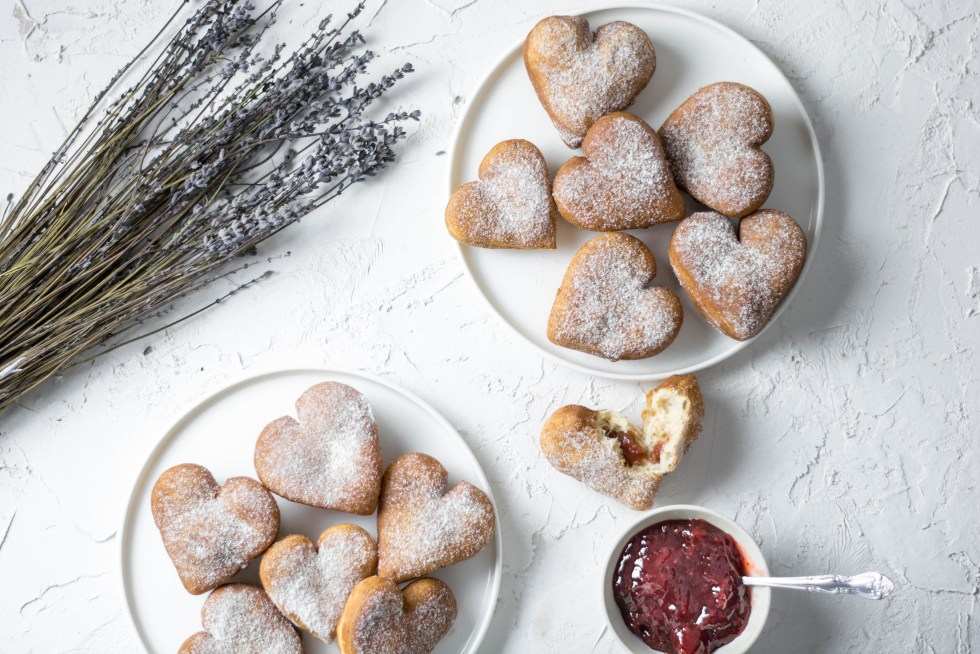 Auf diesem Bild sind zuckerfreie und vegane Herz - Krapfen zu sehen. Die Krapfen wurden von oben fotografiert, daneben steht eine Schüssel mit zuckerfreier Marmelade und frischer Lavendel.