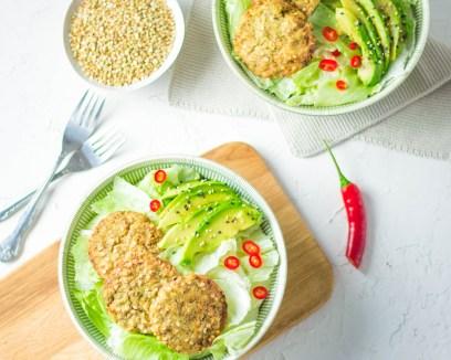 Auf diesem Bild sind vegane Buchweizen - Brokkoli Bratlinge zu sehen. Die Bratlinge liegen in einer Schüssel mit frischem grünen Salt, einer Avocado und Chili.