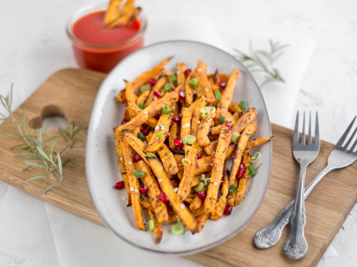 Auf diesem Bild sind gesunde Süßkartoffel - Pommes von vorne fotografiert. Die Pommes liegen auf einem Keramik Servierteller, welches auf einem Holzbrett steht. Im Hintergrund sieht man eine Schale mit Ketchup stehen.