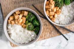 Hier wurde gebratener Brokkoli mit Reis und Tofu von oben fotografiert. Zwischen den beiden beigen Schüsseln liegen Essstäbchen.