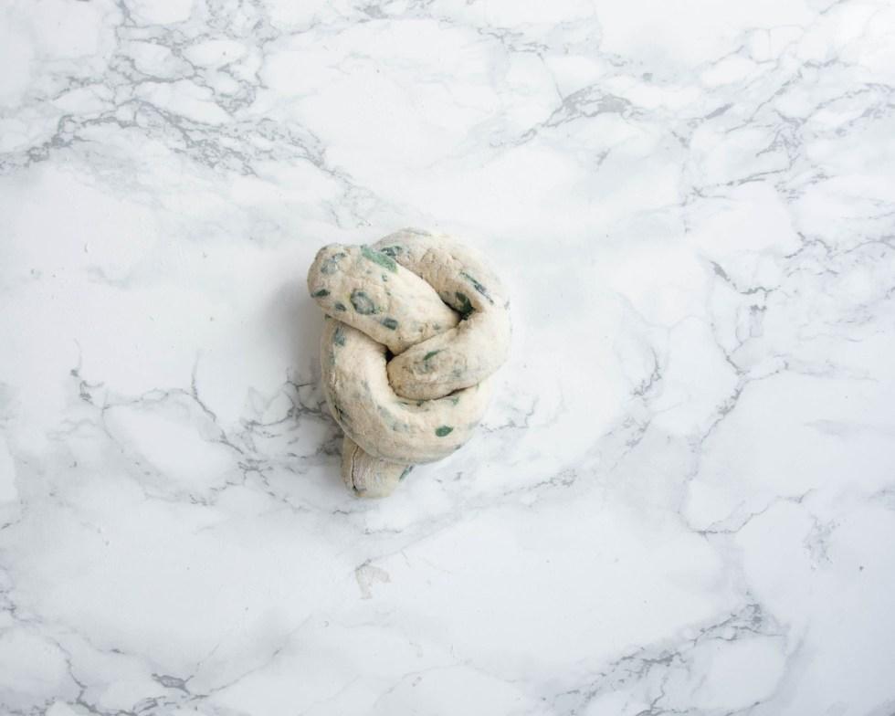 Auf diesem Bild ist das noch nicht gebackene Bärlauch - Knoten Brötchen zu sehen. Im Teig befinden sich viele kleine Bärlauchstückchen und Dinkelvollkornmehl.