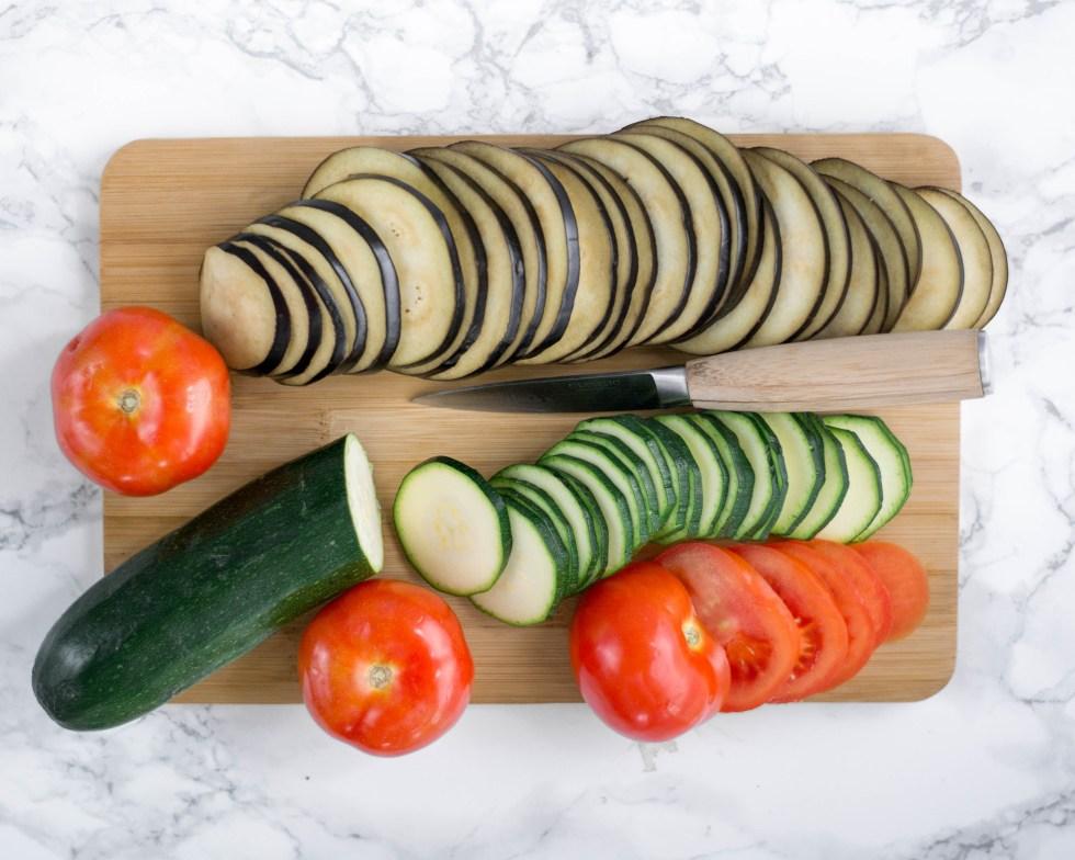 Du kannst sehen wie auf diesem Bild für das Ratatouille aus dem Ofen das Gemüse in dünne Scheiben geschnitten wird. Das Gemüse liegt fein geschnitten auf einem Holzbrett.