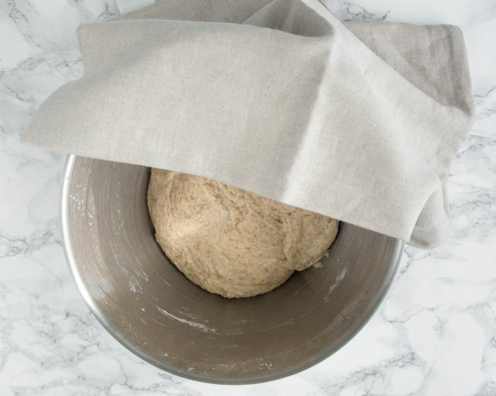 In diesem Bild ist eine Rührschüssel mit einem Teig zu sehen, die mit einem Leinentuch zugedeckt wird. Toastbrot selber machen ist sehr einfach und hier kannst du erkennen, wie der Hefeteig dafür zubereitet wird.