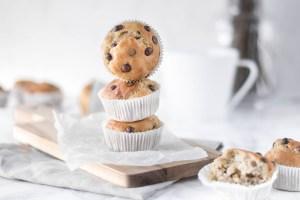 Auf diesem Bild sind zuckerfreie Bananen - Schoko Muffins zu sehen. Die Muffins wurden übereinander gestellt und schön auf einem Holzbrett drapiert.