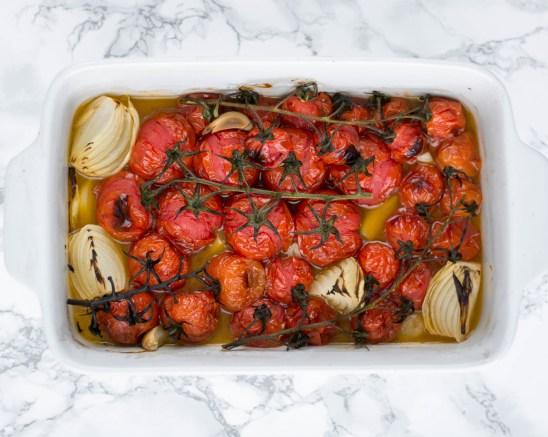 Das Gemüse für die geröstete Tomatensuppe liegt in einer weißen Auflaufform und wurde mit Olivenöl beträufelt.