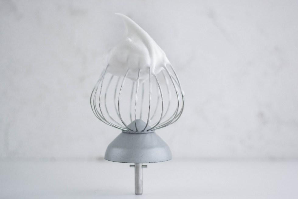 Auf diesem Bild ist ein Schneebesen mit Aquafaba zu sehen. Dieses Bild ist das Titelbild des Beitrages alles über Aquafaba.