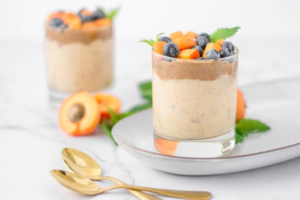 Auf diesem Bild ist ein veganer Marillen - Mandel Porridge zu sehen der von vorne fotografiert wurde. Der Porridge wurde in zwei Gläsern angerichtet und mit braunem Mandelmus, Marillen und Heidelbeeren angerichtet.