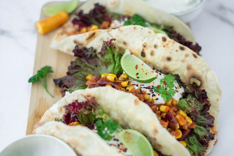 Auf diesem Bild sind Tortillas mit Chili sin carne zu sehen. Das vegane Chili con carne wurde liebevoll auf einem Holzbrett angerichtet.
