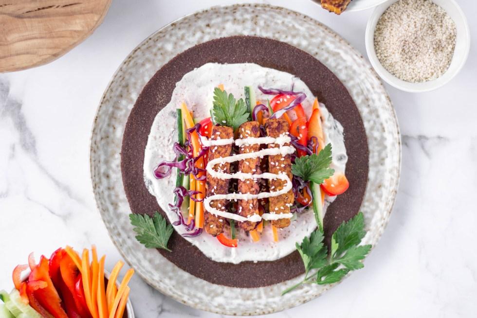 Auf diesem Bild sind schnelle Tempeh Tortillas zu sehen, die auf einem runden Teller angerichtet wurden. Die Tortillas wurden mit Sojajoghurt bestrichen und mit knackigem Gemüse und mariniertem Tempeh belegt.
