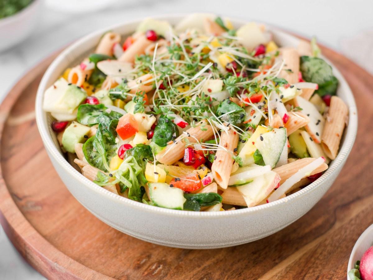 Auf diesem Bild ist ein Nudelsalat mit roter Linsen Pasta zu sehen, der von vorne fotografeiert wurde. Der Nudelsalat wurde in einer Schüssel angerichtet und mit Kresse und Gewürzen dekoriert.